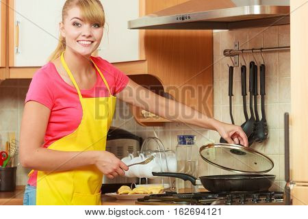 Girl frying breaded cutlet pork chop on fry pan. Young woman in apron cooking preparing dinner food in kitchen.