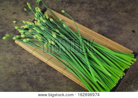 bunch of fresh chives on a wooden cutting board