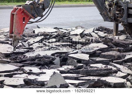 Street roadway reconstruction. Bulldozer and hydraulic breaker divide old asphalt.