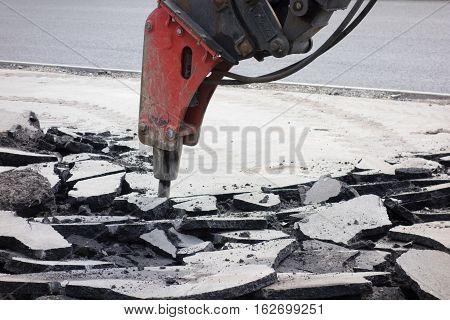 Street roadway reconstruction. Hydraulic breaker divides old asphalt.