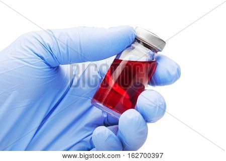medical glove with red liquid in tube on isolated background