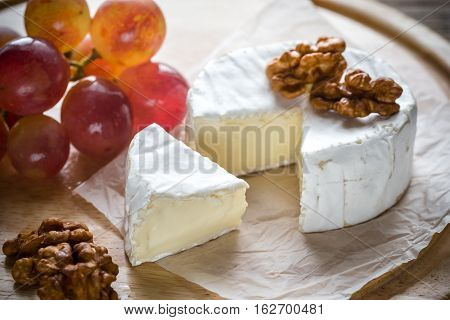 Camembert cheese with walnuts and grape on the wooden board