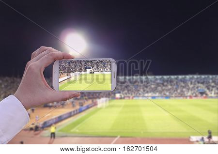 Hand with smart phone in a stadium taking pictures of a sporting event