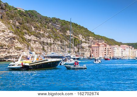 Bonifacio France - July 2 2015: Pleasure yacht with ordinary tourists enters the port of Bonifacio small resort port city of Corsica island in summer sunny day mooring service staff in work