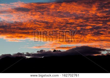 Sunset with orange clouds over the mountains