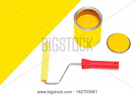 Bank of yellow paint and roller paintbrush on white background with empty space for text.