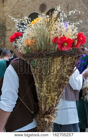 Wicker Basket Filled with Sheafs of wheat and Flowers Carried over the Shoulder of Countryman
