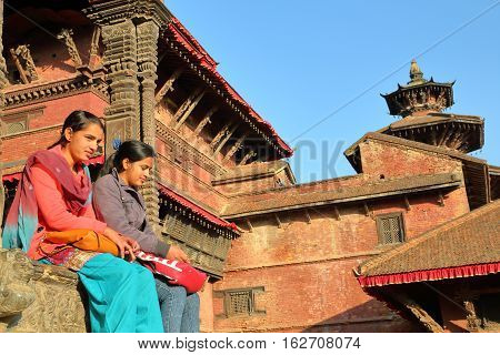 PATAN, NEPAL - DECEMBER 21, 2014: Two young Nepalese women sitting at Durbar Square