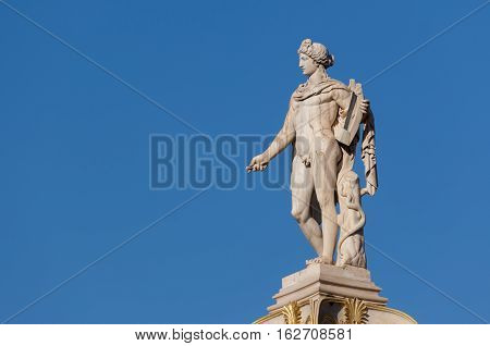 classical Apollo god statue from side, blue sky