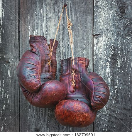 Old boxing gloves hanging on a wooden wall
