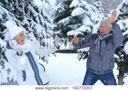 mature couple have fun outdoors near fir trees