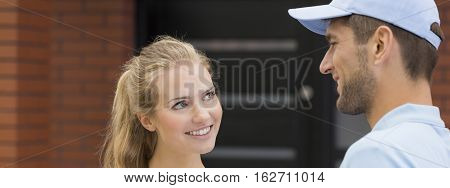 Closeup shot of a young woman talking to a handsome postman