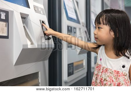 Asian Chinese Little Girl Buying Admission Ticket At Mrt Station