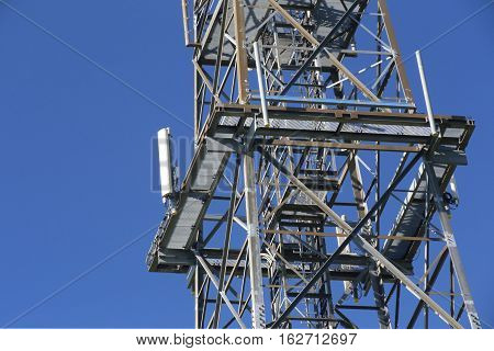 Metal Frame Of Telecommunications Tower In Front Of A Dark Blue Sky