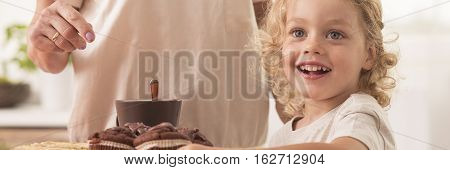 Child In Front Of Muffins