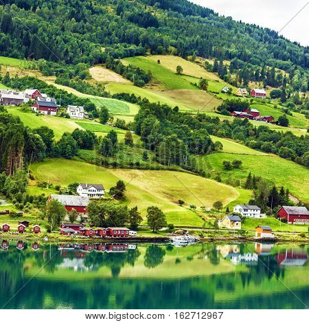 Small town and cruise port Olden in Norwegian fjords. Tourist camping on the beach.
