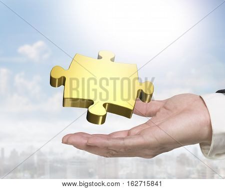 Man Hand Holding Golden Puzzle Piece
