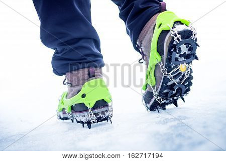 Hiking boots with equipment for ice. Snow like a background and sun. Sun is shining. Moutains and travel.