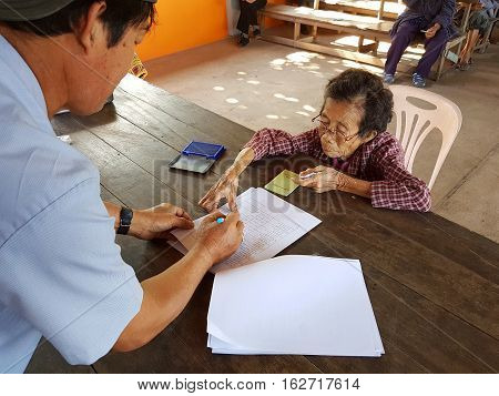 CHIANG RAI THAILAND - DECEMBER 19 : Unidentified asian old woman fingerprinting on paper before treatment on December 19 2016 in Chiang rai Thailand.