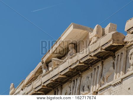 PAST AND PRESENT, STATUE IN THE EAVE OF THE PARTHENON AT THE ACROPOLIS IN ATHENS, GREECE WITH JET TRAIL IN SKY