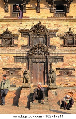 BHAKTAPUR, NEPAL - DECEMBER 29, 2014: Traditional house facade with Nepalese men enjoying the sun