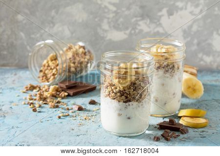 Granola. Granola With Yogurt, Chocolate And Banana On Blue Concrete Table.