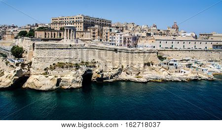 VIEW OF VALLETTA, MALTA FROM THE SEA SHOWING THE ROCK FOUNDATION, CAVERNS, AND SHACKS ON THE SEA