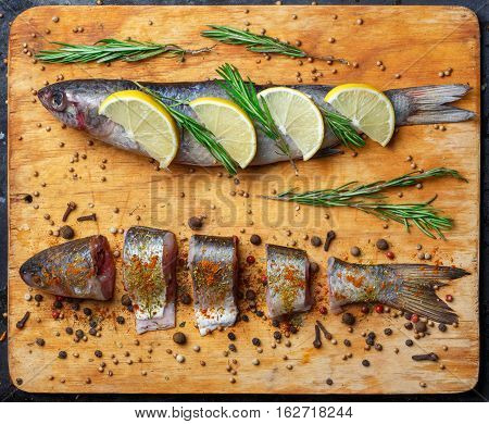 Whole and cut grey mullet fishes lie on light wooden cutting board with lemon segments rosemary branches peppercorns paprika chilli pepper and other spices around. Top view.