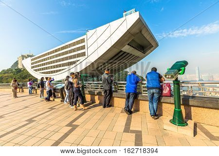 Hong Kong, China - December 7, 2016: Tourists observe the Hong Kong skyline from the free viewing terrace of Peak Galleria, a gigantic shopping center in front of the Peak Tower.