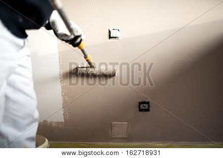 Handy Man Decorating Walls With Paint. Construction Plaster Worker Painting And Renovating With Prof