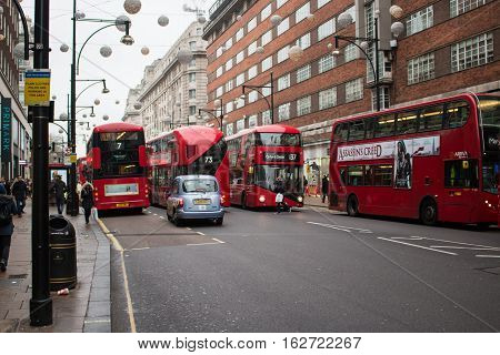 London, UK - December 19, 2016: Red double decker buses on busy Oxford Street in Christmas period