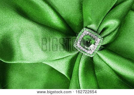Emerald ring on draped green satin as a background