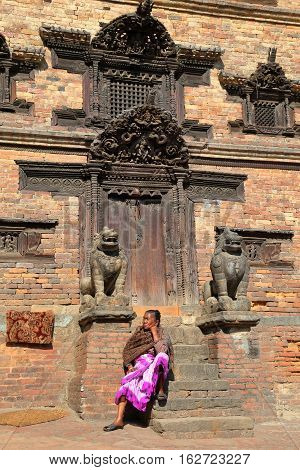 BHAKTAPUR, NEPAL - DECEMBER 30, 2014: A Nepalese woman sitting in front of a traditional house
