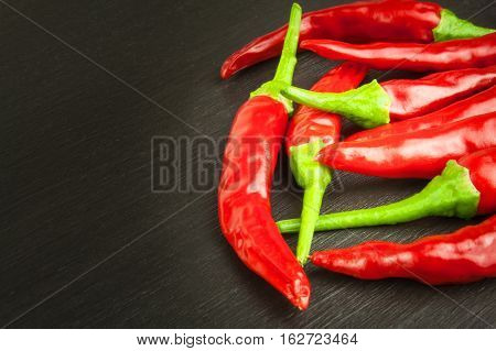 Red chilly pepper on wooden black background. Red hot chili peppers.  Domestic cultivation extra hot chilli burn. Growing chili peppers. Spicy seasoning food. Healthy spices.