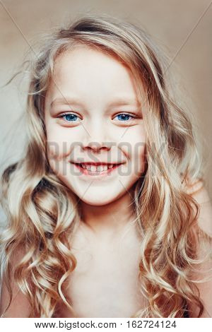 Little cute blonde girl with curls and blue eyes.