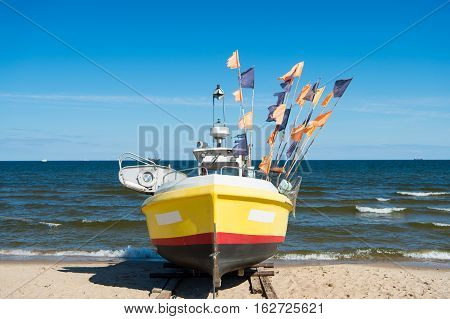 boat or ship modern marine vessel with colorful flags at moorage on beach on sunny day on blue sea and sky background