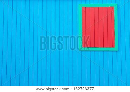 bright colorful wooden blue wall of house with closed red window in green frame as textured abstract background copy space