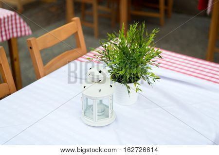 cozy summer outdoor cafe with green bouquet in vase and candle on table with tablecloth with nobody
