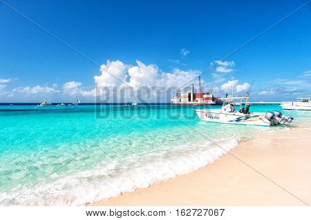 Grand Turk Turks and Caicos Islands - December 29 2015: big cargo ship red color with crane and many containers on ocean water and blue cloudy sky background motor boat on sandy beach sunny outdoor