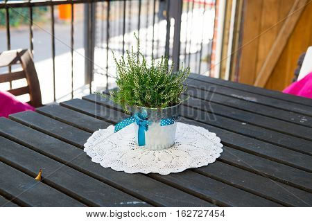cozy summer outdoor cafe with green bouquet in vase on wooden table and napkin with nobody