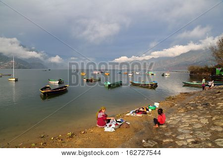 POKHARA, NEPAL - JANUARY 3, 2015: Nepalese woman washing clothes along the shore of Phewa Lake