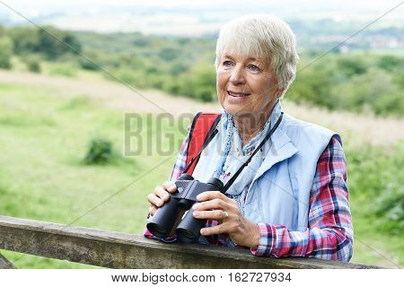 Senior Woman On Birdwatching Walk With Binoculars