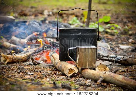 Tea cooked on the fire. Bowler and mug with hot water stand on the wood. Focus on mug. In the background burns the fire.