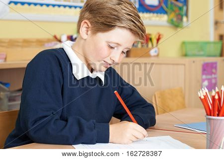 Male Elementary School Pupil Working At Desk