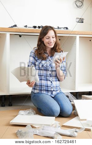 Smiling Woman Assembling Units In New Kitchen