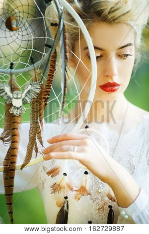 Outdoor portrait of a beautiful model girl with dream catcher vintage and retro tone, soft focus. Full red lips.