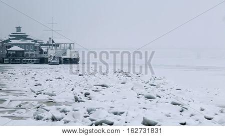 Frozen river, broken ice blocks. Broken ice blocks in the foreground. Docks in the background.