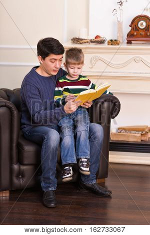 kid boy and his father read a book at home.