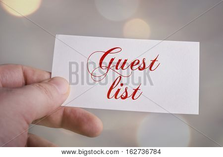 Guest list card in hand with bokeh lights background