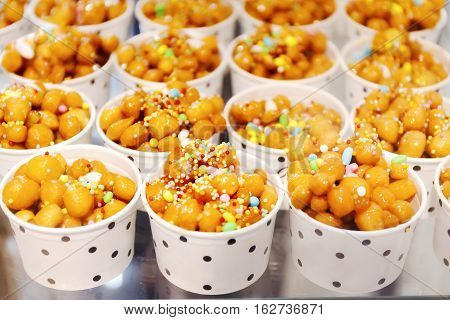 Cups filled with Struffoli typical Neapolitan pastry consisting of many small balls of dough (realized on paper with flour eggs lard sugar anise liqueur) fried in oil and wrapped in warm honey. Decorated with colored sprinkles.